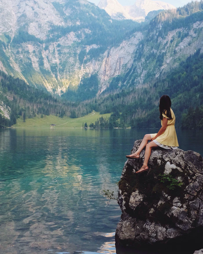 A woman sits on a rock overlooking a scenic lake.