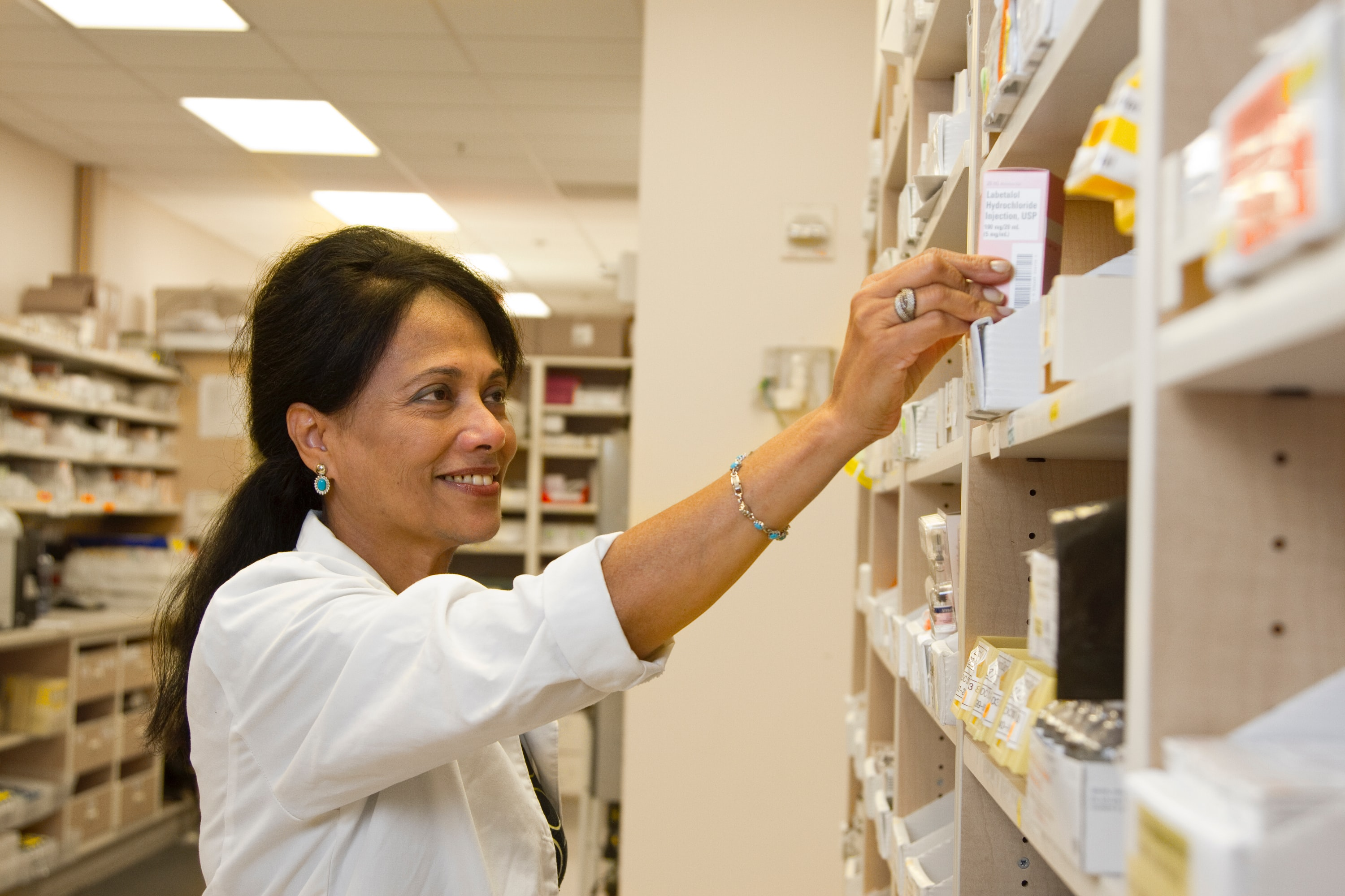 A pharmacist in one of the legit online pharmacies pulls a dispensing box of medication from a shelf.