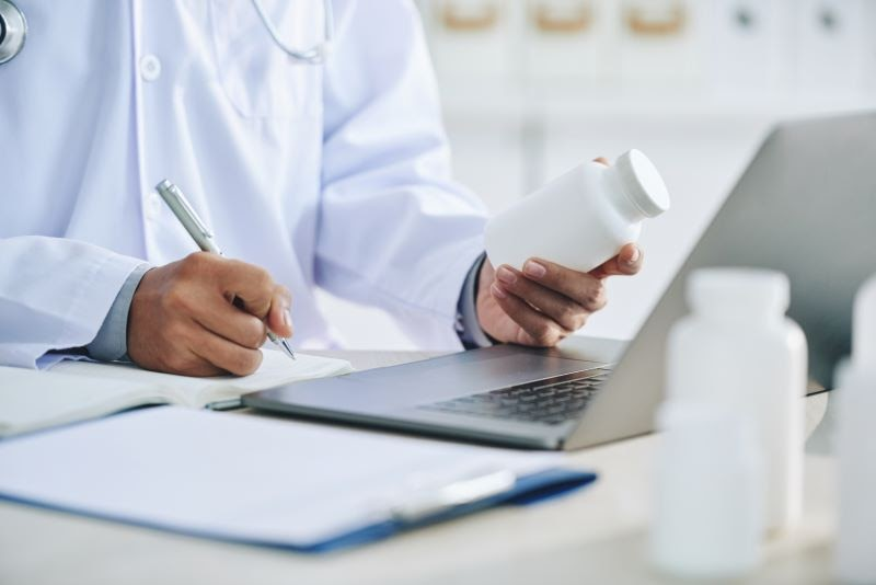 A doctor prescribing medication while complying with pharmaceutical regulations and laws